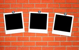 Blank old photos on clips on brick wall Stock Image