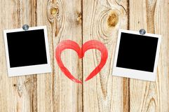 Blank old photos on clips and red heart on color wooden backgrou Stock Images