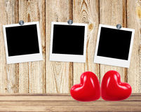 Blank old photos on clips and red hearts on wooden background Stock Photography