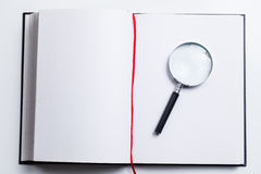 Blank open book and magnifying glass Royalty Free Stock Images