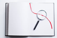 Blank open book and magnifying glass Stock Photos