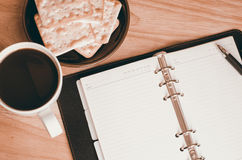 Blank open notebook with cup of coffee and biscuit on table Stock Image
