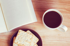 Blank open notebook with cup of coffee and biscuit on table Royalty Free Stock Image