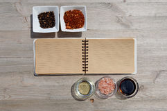 Blank open notebook for notes and pepper, bay leaf, rosemary, onions, Himalayan salt, olive oil, soy sauce on a w Royalty Free Stock Photos