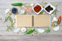 Blank open notebook for notes and pepper, bay leaf, rosemary, onions, salt, olive oil, soy sauce on a wooden table Royalty Free Stock Photos