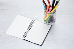 Blank open notebook with pencil crayons Stock Images