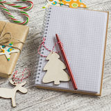 Blank open Notepad, Christmas gifts, candies on a wooden surface Royalty Free Stock Photos