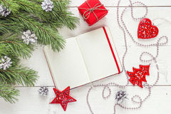 Blank open notepad, pine branches and Christmas decorations on a. White wooden table. Space for text. Top view. Flat lay style royalty free stock image
