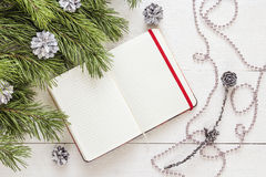 Blank open notepad, pine branches and Christmas decorations on a. White wooden table. Space for text. Top view. Flat lay style royalty free stock photos
