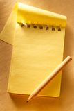 Blank open yellow notepad with pencil Stock Images