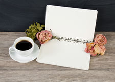 Blank opened notepad with copyspace, cup of coffee and roses on Stock Images