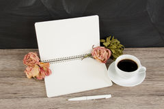 Blank opened notepad with copyspace, cup of coffee and roses on Royalty Free Stock Images