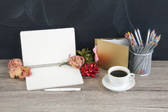 Blank opened notepad with copyspace; cup of coffee; stack of pen Stock Image