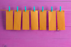 Blank orange note pad sheets hanging from string Stock Photography