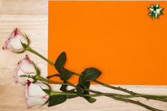 Blank orange page with white rose on a wooden background. Copy space Royalty Free Stock Images