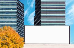 Blank outdoor billboard mockup with modern business buildings. Blank large outdoor billboard mockup with modern business buildings in background on bright autumn stock image