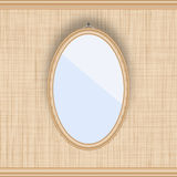 Blank oval picture frame on a beige wall with fabric texture. Stock Photo