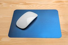 Blank pad and wireless computer mouse. On wooden background Royalty Free Stock Image