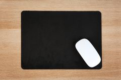 Blank pad and wireless computer mouse. On wooden background, top view Stock Photo