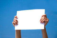 Blank page in hands, billboard. Person holding a blank page in its hands with blue sky background Royalty Free Stock Photos