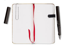 Blank page of note book with paper clip. And elastic strap and old fountain pen, isolated on white Royalty Free Stock Image