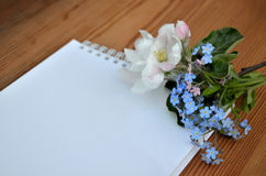 Blank page of a notebook and bouquet of forget-me-nots Royalty Free Stock Image