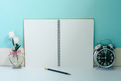 Blank page notebook with flowers and shiny metal clock with a pe royalty free stock image