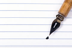 Blank page and pen. A blank page that is open with a calligraphy pen on top royalty free stock photo