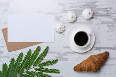 Blank page on rustic wooden background with croasant, coffee, marshmallows. Vintage mockup with text place Royalty Free Stock Image