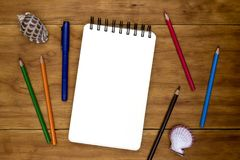 Blank page of spiral notepad on wooden table. Crayon pencil and pen flat lay photo. Empty sketchbook page table top view stock images