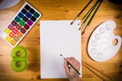 Blank page on the table with palette and childs hand Royalty Free Stock Photo