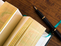 Blank pages of open journal with pen. Blank pages of an open journal with pen lying next to it on desk, shallow depth of field with focus on foreground pages stock photography