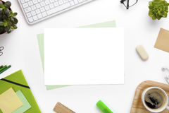 Blank Pages Surrounded With Office Supplies On White Desk. Overhead view of blank pages surrounded with office supplies on white desk Stock Photography