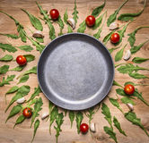 Blank pan with tomatoes and herbs around place for text, frame on wooden rustic background top vie Royalty Free Stock Photo