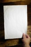 Blank paper. Old blank paper held by a hand Royalty Free Stock Photo