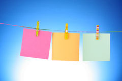 Blank paper. Sheets on a clothes line on a blue background Stock Photos