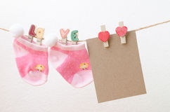 Blank paper with baby socks hanging on love clothesline.  Royalty Free Stock Photo