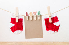 Blank paper with baby socks hanging on love clothesline Royalty Free Stock Images