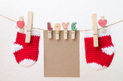 Blank paper with baby socks hanging on love clothesline.  Stock Image