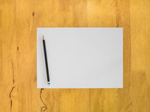 Blank paper and black pencil on wooden table. Blank paper and black pencil on wooden table from Top view with Education concept Royalty Free Stock Photos