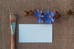 Blank paper, brush and flower on sacking Stock Photos