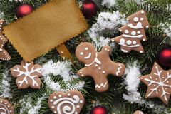 Blank paper card and Christmas gingerbread cookies on snow stock images