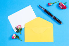Blank paper card, envelope, pen and rose on blue background Royalty Free Stock Image