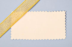 Blank paper card with gold ribbon. Blank paper card with gold ribbon for your text on gray background Royalty Free Stock Photos