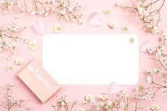 Blank paper card with gypsophila flowers and gift box on pink ba