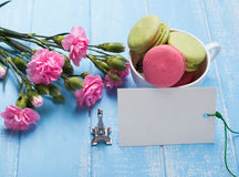 Blank paper card, macarons, flowers and souvenir Eiffel tower on Royalty Free Stock Photos