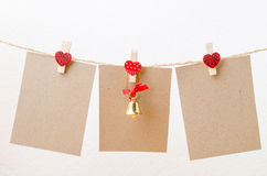 Blank paper and christmas bell hanging on heart clothesline with Royalty Free Stock Photos