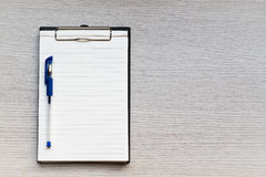 Blank paper in clipboard and pen on wooden table Stock Photos