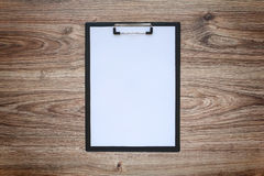 Blank paper in clipboard on wooden table Stock Image