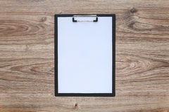 Blank paper in clipboard on wooden table Royalty Free Stock Photography